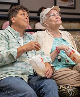 a senior woman enjoying a movie with a younger woman